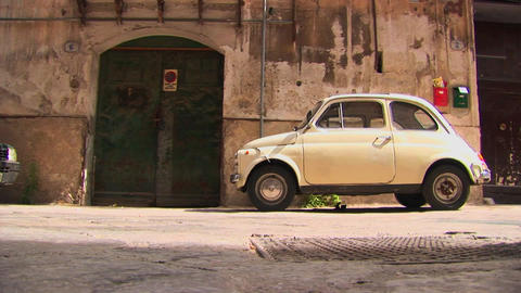 A small car parked outside an old stone building Palermo, Italy Footage
