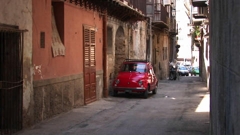 Cars parked along stone buildings in a tightly spaced... Stock Video Footage