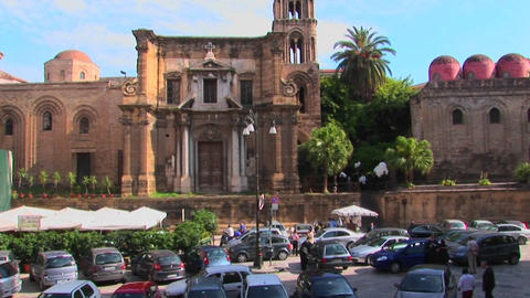 Many cars are parked in front of a religious building made of stone Palermo, Italy Footage