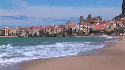 Small waves break near houses along a shoreline in Cefalu, Italy Footage