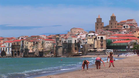 Small waves break near houses along a shoreline as children play in the sand in Cefalu, Italy Footage