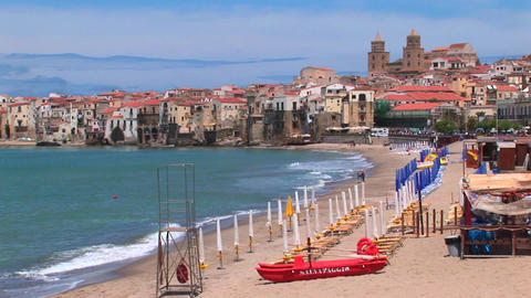 A small boat and umbrellas rest on a beach with houses near the shoreline in Cefalu, Italy Footage