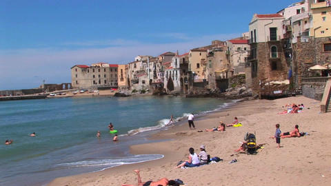 Small ocean waves break near houses as families relax... Stock Video Footage