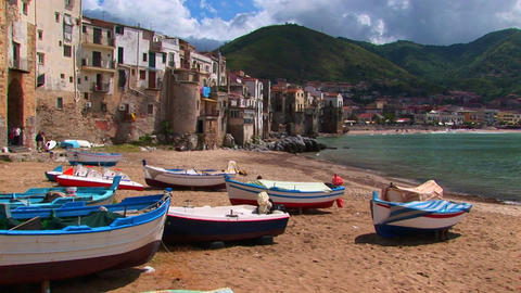 Boats on a beach next to the ocean and houses in Cefalu, Italy Footage