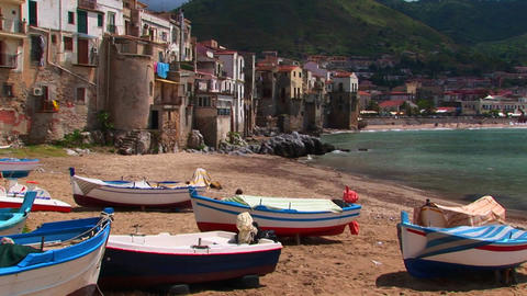 Boats on a beach next to the ocean and houses in Cefalu,... Stock Video Footage