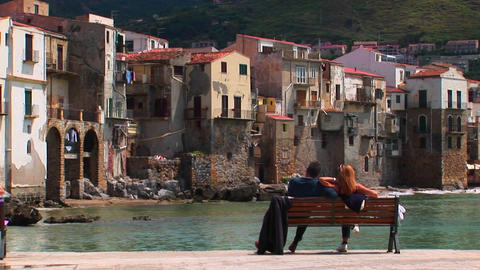 A couple sits on a bench overlooking the ocean and houses... Stock Video Footage