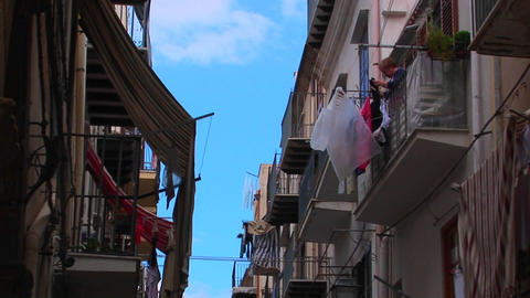 A man hangs clothing from his balcony across from other... Stock Video Footage