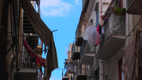 A man hangs clothing from his balcony across from other apartment buildings in Cefalu, Italy Footage