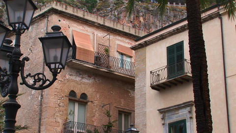 Street lamps and brick buildings are within close proximity of one another in Cefalu, Italy Footage