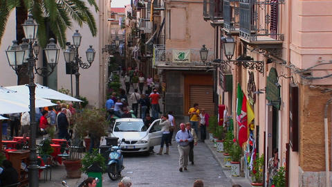 Pedestrians walk pass lamps and brick buildings within close proximity of one another in Cefalu, Ita Footage