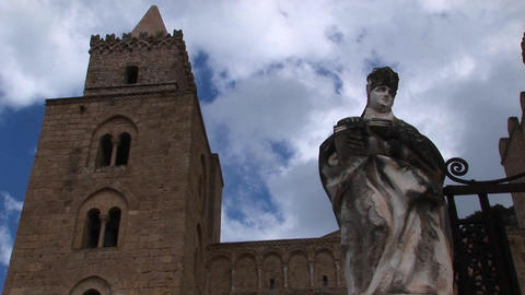 A cloud time lapse moving above a statue of a woman holding a book and a building in Cefalu, Italy Footage