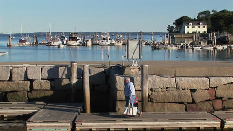 Boats are seen in the distance as a man walks along a pier in Maine Footage