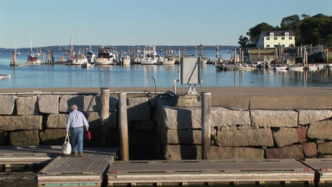 Boats are seen in the distance as a man walks along a... Stock Video Footage