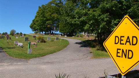 A dead end sign near a cemetery on a hillside Live Action