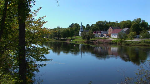 A lake reflects a peaceful countryside at a New England... Stock Video Footage