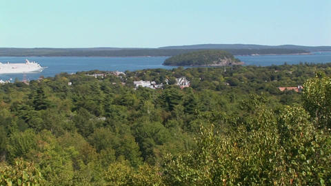 A white cruise ship is seen in the distance of a forest in Bar Harbor, Maine Footage