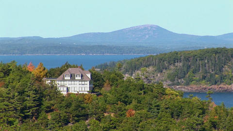 A house and islands are seen in the distance of a forest in Bar Harbor, Maine Footage