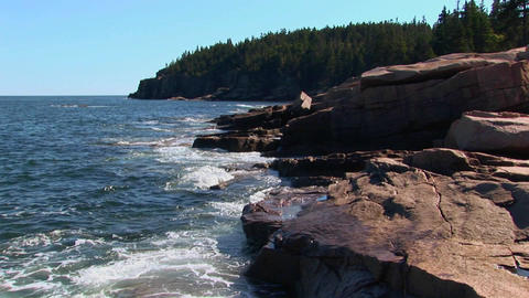 Water crashes against rocks that are near trees and a... Stock Video Footage