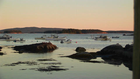The silhouette of a lobster village near sailboats at anchor in a Stonington, Maine Footage