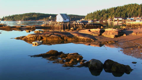 A lobster village building over water as seen from a rocky shore in Stonington, Maine Footage