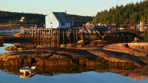 A lobster village building in Stonington, Maine is over water and near a rocky shore Footage