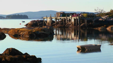 Rocks and a pier are near a lobster village in Stonington, Maine at sunset Footage