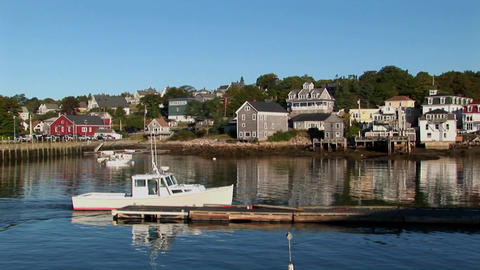 A boat stops at a dock next to a man near a lobster village in Stonington, Maine Footage