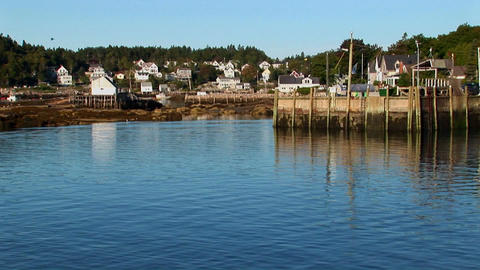 A boat passes a pier and lobster village in Stonington,... Stock Video Footage