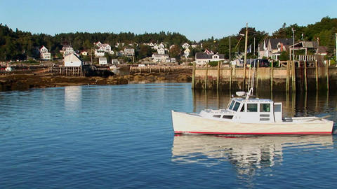 A boat passes a pier and lobster village in Stonington, Maine Footage