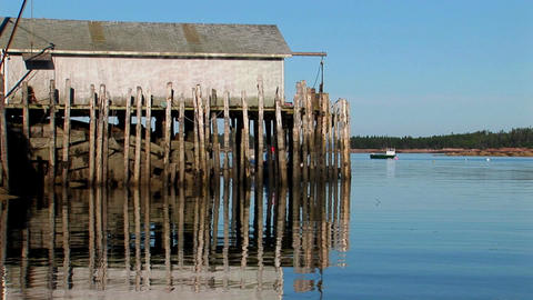 At a lobster village in Stonington, Maine a building is held over water by wooden pillars and rocks Footage