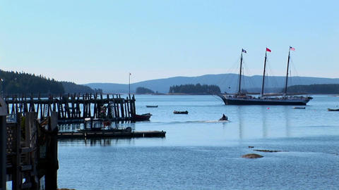 A sailing ship is at anchor near a wooden pier offshore a lobster village in Stonington, Maine Footage