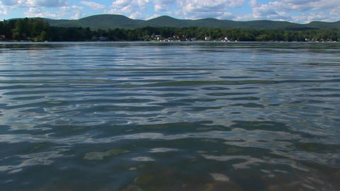Mountains and trees are seen in the distance of a glassy rural lake in Central Vermont Footage