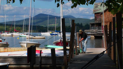 A man ties his boat to a wooden dock on a rural lake in Central Vermont Footage