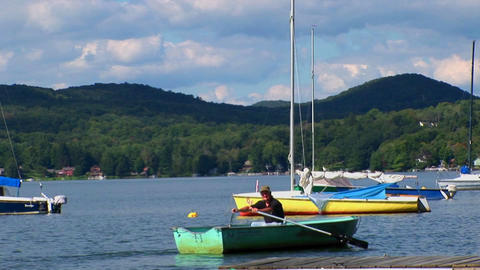 A man drifts in a rowboat near sailboats and a dock on a rural lake in Central Vermont Footage