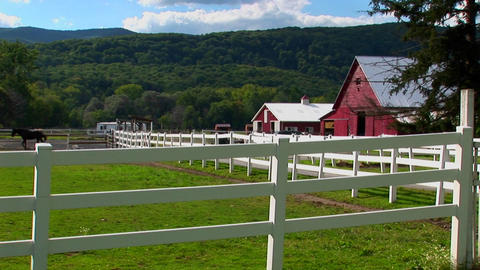 A horse in the background of a white fence and red barn at day in Vermont Footage