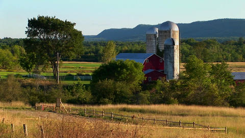 A barn near a field and trees at day in Vermont Stock Video Footage