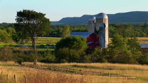 A barn near a field and trees at day in Vermont Footage