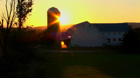 The silhouette of a barn at sunset Footage