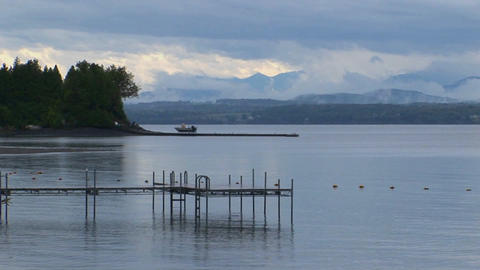 A small dock extends into calm waters below a grey and... Stock Video Footage