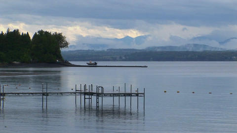A small dock extends into calm waters below a grey and cloudy sky at Lake Champlain in Vermont Footage