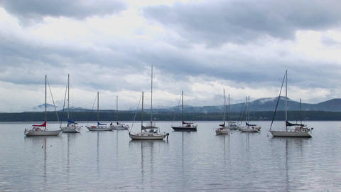 Clouds cover a mountain range in the distance of sailboats on calm water at Lake Champlain in Vermon Footage