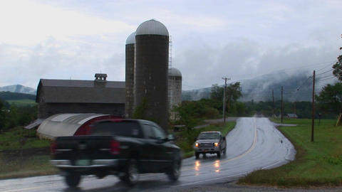 Vehicles drive pass a barn on a cloudy and rainy day Stock Video Footage