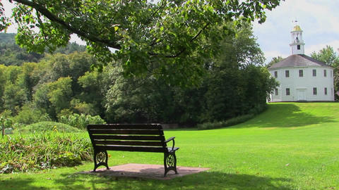 A bench overlooks green grass that leads to a golden... Stock Video Footage