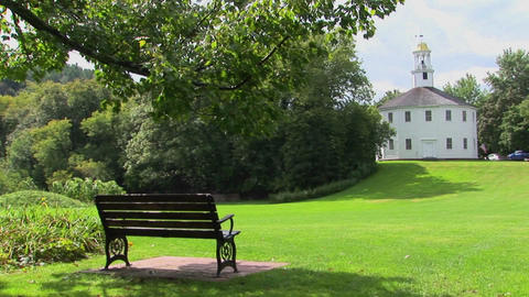 A bench overlooks green grass that leads to a golden domed white building in Vermont Footage