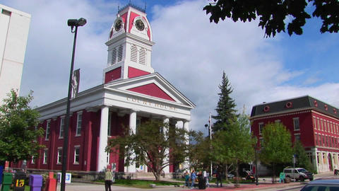 Pedestrians and vehicles travel pass a historic court house in Montpelier, Vermont Footage