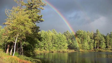 A rainbow over a forest and near a lake in Rural Maine Footage