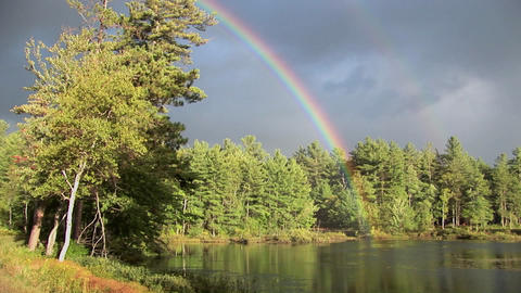 A rainbow over a forest and near a lake in Rural Maine Stock Video Footage