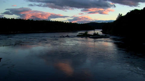 Clouds at sunset move above dark waters and the silhouette of forests in Rural Maine Footage