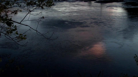 The reflective surface of dark water ripples slowly in Rural Maine Footage