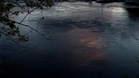 The reflective surface of dark water ripples slowly in... Stock Video Footage